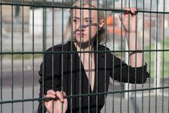 Blonde girl in a black coat behind a metal fence stock photography
