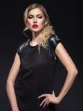Blonde girl in black dress Stock Photos