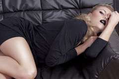 Blonde girl in a black dress laying on a couch Royalty Free Stock Photos