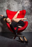 Blonde girl in black dress lies on the red armchair Royalty Free Stock Photography