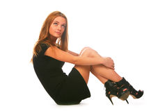Blonde girl in the black dress, sitting on a white Royalty Free Stock Images