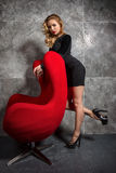 Blonde girl in a black dress standing near red armchair. Stock Photography