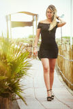 Blonde girl with black dress walking along a path Stock Photos