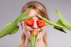 Blonde girl blinded by flowers. Royalty Free Stock Image