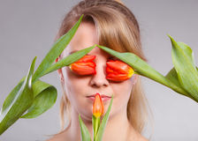 Blonde girl blinded by flowers. Royalty Free Stock Photo