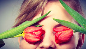 Blonde girl blinded by flowers. Royalty Free Stock Images