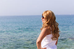 Blonde girl. Looking at sea, Athens Greece royalty free stock photo
