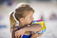 Blonde girl (3-5) blowing air into inflatable armband on beach, side view, close-up Stock Photos