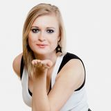 Blonde girl blowing a kiss or with copy space on h Royalty Free Stock Images