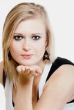 Blonde girl blowing a kiss or with copy space on hand Royalty Free Stock Image