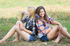 Blonde girl blowing multicolor soap bubbles near her brunette friend Royalty Free Stock Images
