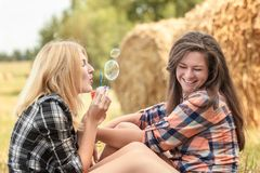 Blonde girl blowing soap bubbles Royalty Free Stock Photography