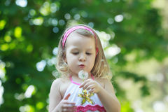 Blonde girl blowing on white Taraxacum officinale Royalty Free Stock Image
