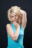 Blonde girl in blue 02. Blonde girl in blue blouse against black backgound royalty free stock images