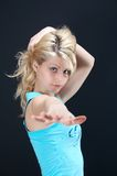 Blonde girl in blue. Blouse against black backgound Royalty Free Stock Photography