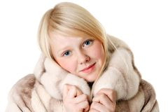 Blonde girl with blue eyes wearing a fur coat Royalty Free Stock Image