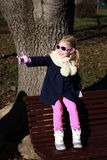 Blonde girl with blue jacket and pink sunglasses sitting and playing on bench in park Royalty Free Stock Photo
