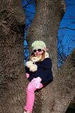 Blonde girl with blue jacket and pink sunglasses sitting and playing in a tree park Royalty Free Stock Photo