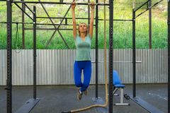 Blonde girl in blue leggings and a T-shirt keeps his arms outstretched for the horizontal bar pulling up aloft in an outdoor gym stock photo