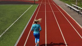Sportive blonde woman running at open stadium. Blonde girl in a blue sportswear and sneakers is running on the track at the stadium outdoors. Sun is shining onto stock footage