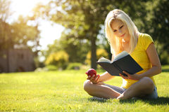 Blonde Girl with Book and Apple on Green Grass. Royalty Free Stock Photos