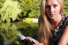 Blonde girl with book on green background of city park Stock Photos