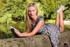 Blonde girl with book on green background of city park Royalty Free Stock Photos