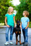 Blonde girl and boy posing with beloved dog or Royalty Free Stock Photo