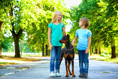 Blonde girl and boy posing with beloved dog or Stock Photo