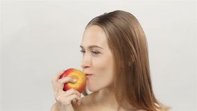 Blonde girl with braces eating apple. White. Closeup. Slow motion stock footage