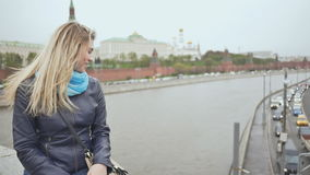 A blonde girl from the bridge sends an air kiss to motorists against the backdrop of the Kremlin. Moscow. Russia stock video footage