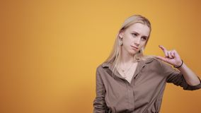Blonde girl in brown blouse over isolated orange background shows emotions stock video