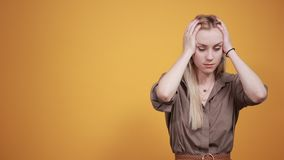 Blonde girl in brown blouse over isolated orange background shows emotions. Young beautiful blonde girl in brown blouse over isolated orange background suffering stock video footage