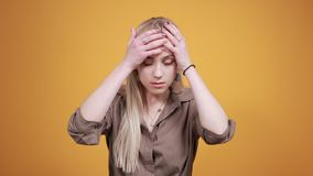 Blonde girl in brown blouse over isolated orange background shows emotions. Young beautiful blonde girl in brown blouse over isolated orange background suffering stock footage