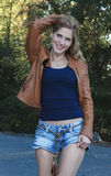 Blonde girl in a brown leather jacket. And denim shorts Stock Image