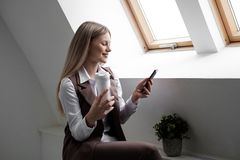 Blonde girl in a business suit works on a computer in a white bright office. royalty free stock image
