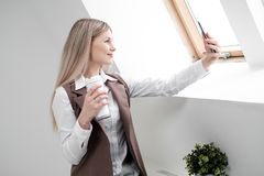Blonde girl in a business suit works on a computer in a white bright office. stock photo