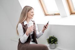 Blonde girl in a business suit works on a computer in a white bright office. royalty free stock photography