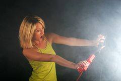 Blonde girl with cables for starting an engine with smoke Stock Photography
