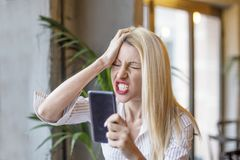 Blonde girl in cafe. Upset blonde girl with mobile phone on her hands in cafe stock photography