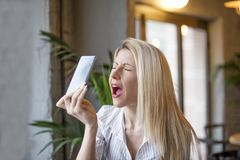 Blonde girl in cafe. Upset blonde girl with mobile phone on her hands in cafe royalty free stock images
