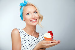 Blonde girl with cake. Portrait of smiling beautiful pinup woman. Girl holding sweet cake Royalty Free Stock Photography