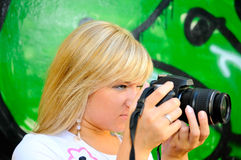 Blonde girl with camera Royalty Free Stock Image