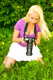 Blonde girl with camera Stock Image