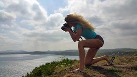 Blonde girl with a camera shooting sea from edge cliff royalty free stock photos