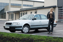 Blonde girl with a car at empty parking place. Blonde girl with a silver car at empty parking place Stock Photo