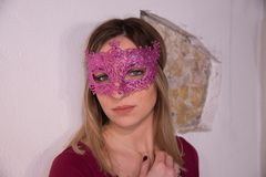 Blonde girl with carnival mask over white background. Masquerade. Portrait of Beautiful Blond Woman in a Carnival Mask. Masquerade. Girl. Beauty & Fashion stock photography