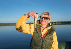 Blonde girl catched a smelt in the sea Stock Images