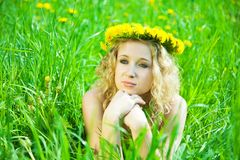 Blonde girl in chaplet. Lying at meadow Royalty Free Stock Photo