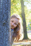 Blonde girl check and looks from behind a tree. In the autumn park Stock Photos